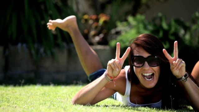 vídeos de stock, filmes e b-roll de mulher deitada na grama rindo para câmera - símbolos de paz