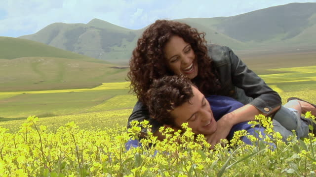vídeos de stock, filmes e b-roll de ws woman lying on top of man in field of yellow wildflowers / castelluccio, norcia, italy - jaqueta jeans