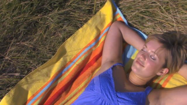 woman lying on towel, uk - liegen stock-videos und b-roll-filmmaterial
