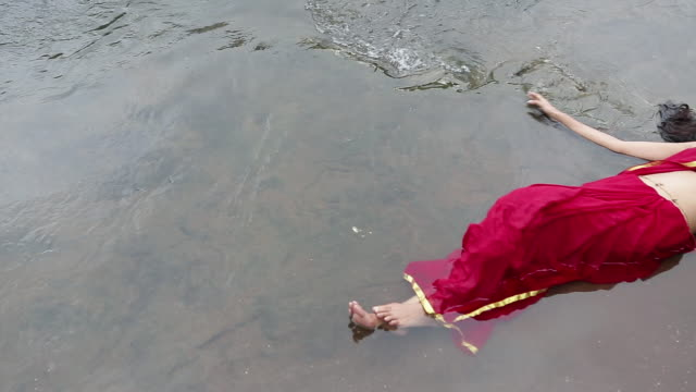 Woman lying on water, Malshej Ghat, Maharashtra, India