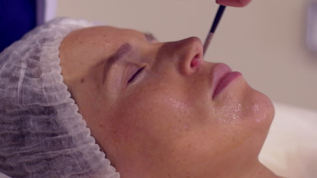 woman lying while cosmetologist applying facial mask with brush - beautician stock videos and b-roll footage