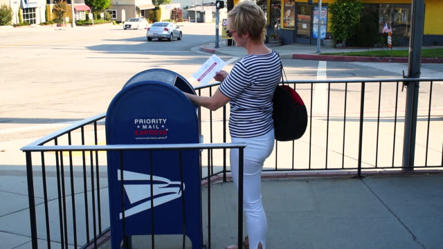 woman mailing a vote by mail envelope - letterbox stock videos & royalty-free footage