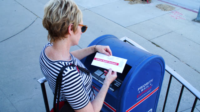 stockvideo's en b-roll-footage met woman mailing a vote by mail envelope - verkiezing