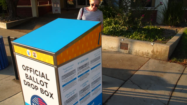 woman mailing her absentee ballot at the official ballot drop box - united states postal service stock videos & royalty-free footage