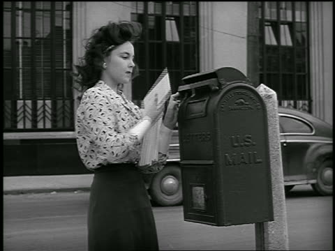 vídeos de stock, filmes e b-roll de b/w 1948 woman mailing letter in mailbox on city street / industrial - sending