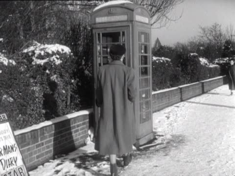 a woman makes a call from a public telephone box - 電話ボックス点の映像素材/bロール