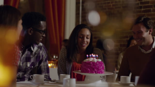 Woman makes a wish and blows out candles on birthday cake as friends clap