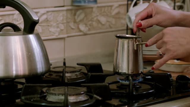 Woman makes coffe in coffe pot