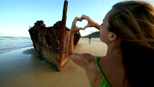 woman makes heart shape finger frame on fraser island - shipwreck stock videos and b-roll footage