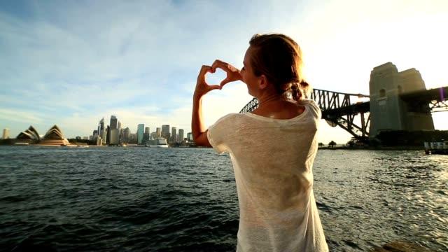 Woman makes heart shape finger frame on Sydney skyline