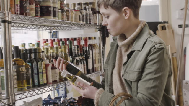 Woman makes her choice between 2 bottles of olive oil in delicatessen shop.