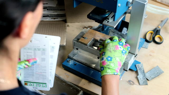 stockvideo's en b-roll-footage met vrouw maakt gaatjes in de verpakking. - productielijn werker