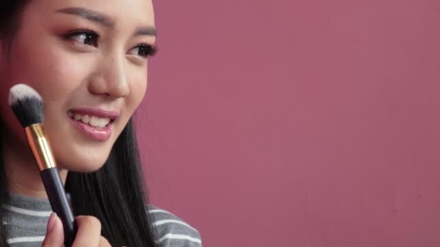 vidéos et rushes de la femme fait le maquillage. jeune femme d'asie fait rougir sur le visage utilisant la brosse de maquillage. concept cosmétique - seulement des jeunes femmes