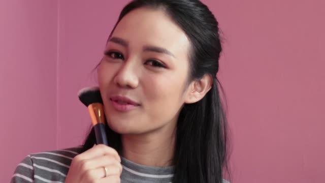 女性は化粧をします。若いアジアの女性は、メイクアップブラシを使用して顔に赤面します。化粧品のコンセプト - 頭点の映像素材/bロール