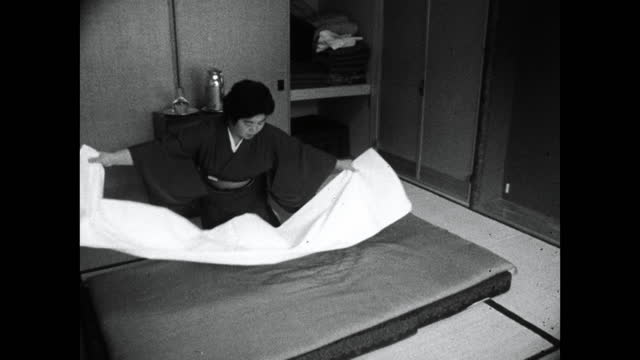 woman makes up a futon bed in hotel room in japan; 1964 - cabinet stock videos & royalty-free footage