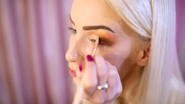 woman make-up artist applying make up on eyes - tutorial stock videos and b-roll footage