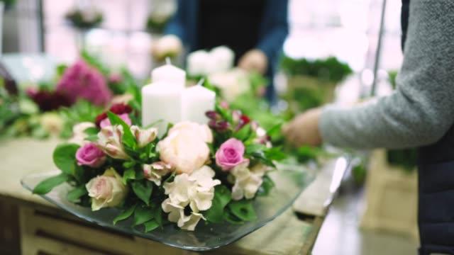 vídeos de stock e filmes b-roll de woman making a beautiful bouquet with candles - ramo parte de uma planta