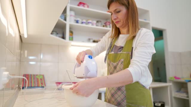vídeos de stock e filmes b-roll de woman making a cake in domestic kitchen - domestic kitchen
