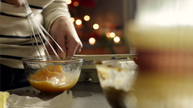 Woman Making a Christmas Cake Whisking Eggs Together in Bowl