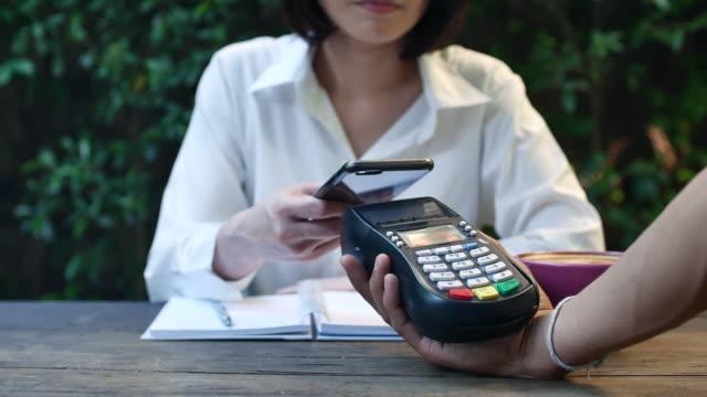Frau macht ein kontaktloses Bezahlen mit Handy im café