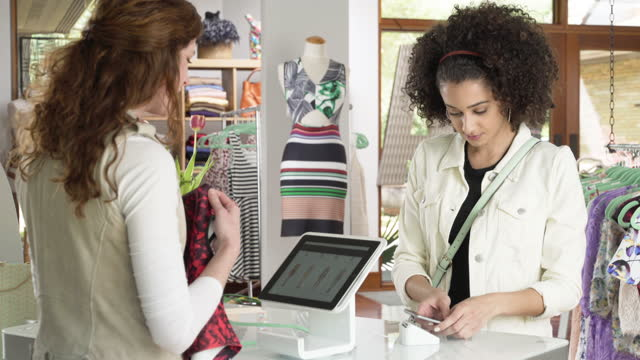vidéos et rushes de woman making a contactless payment with smart phone - paiement mobile