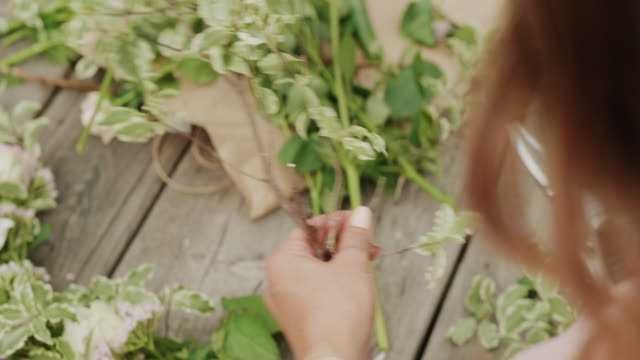 woman making a flower crown on midsummer in sweden - wreath stock videos & royalty-free footage