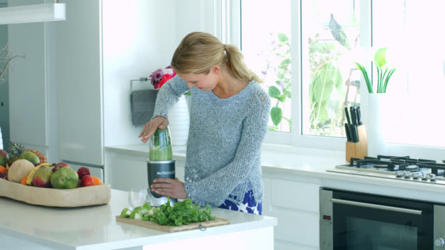 a woman making a green vegetable juice in blender - urbanlip stock videos & royalty-free footage