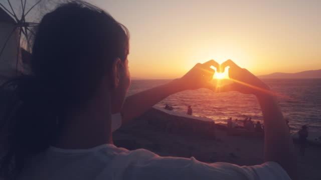 Woman making a heart shape while admiring the seascape.