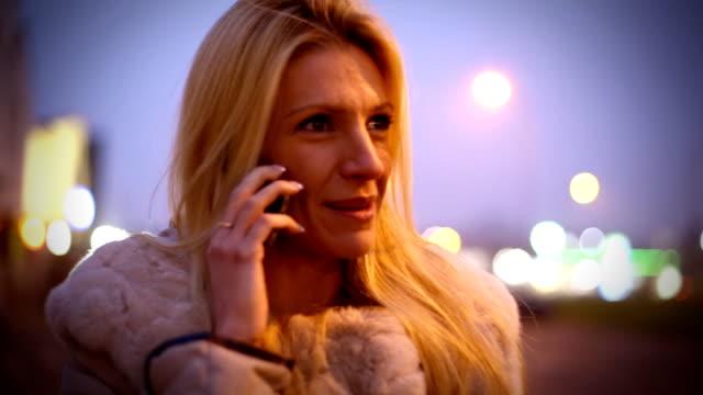 Donna facendo una telefonata in strada al tramonto.