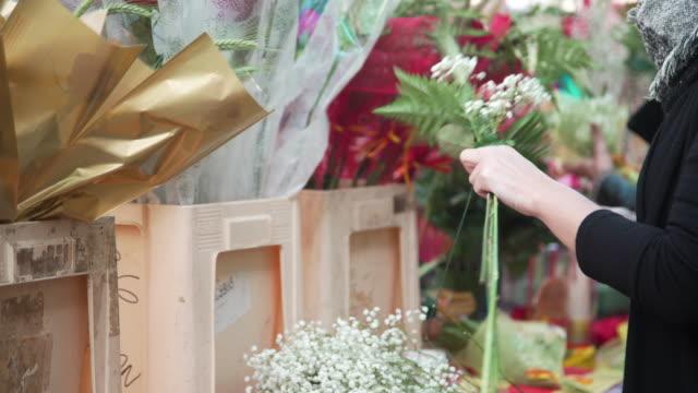 Woman making a rose bouquet at Barcelona street market