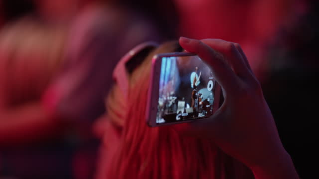 vídeos de stock, filmes e b-roll de woman making a smartphone video at a concert - filmando