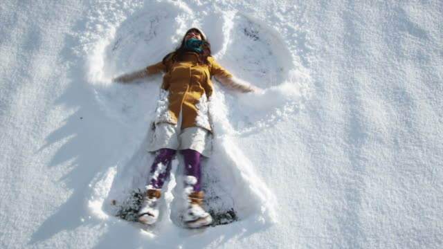 woman making a snow angel - weihnachten stock-videos und b-roll-filmmaterial