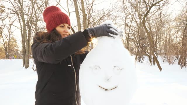 woman making a snowman. - making a snowman stock videos & royalty-free footage
