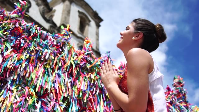 vídeos de stock e filmes b-roll de woman making a wish with brazilian ribbons on church fence in salvador, bahia, brazil - sorte
