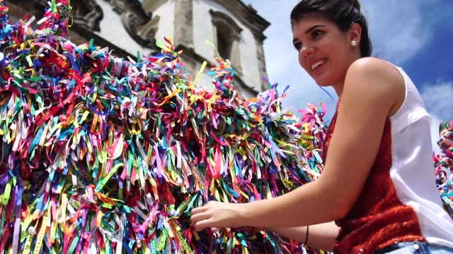 woman making a wish with brazilian ribbons on church fence in salvador, bahia, brazil - tradition stock videos & royalty-free footage