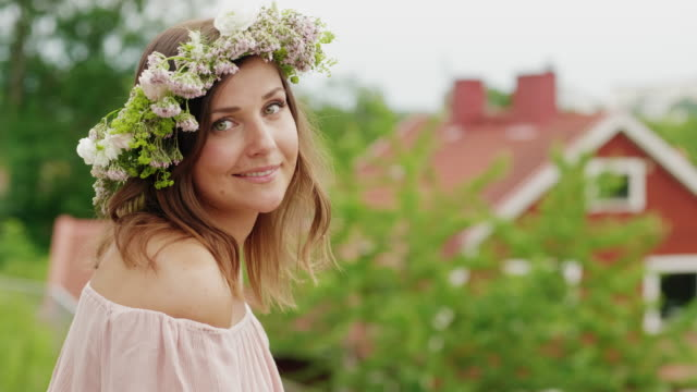 woman making and wearing a flower crown on midsummer in sweden - crown headwear stock videos and b-roll footage
