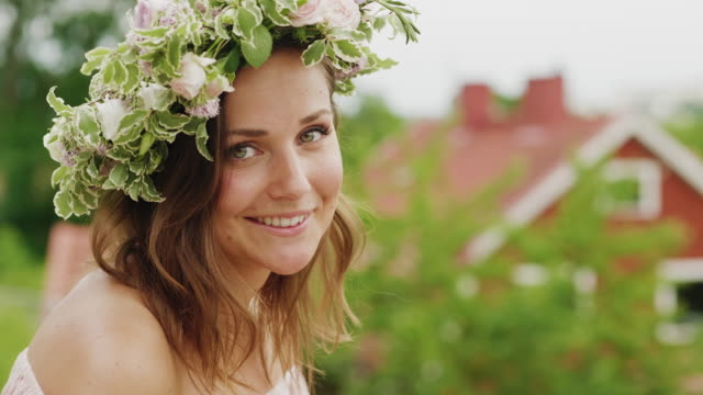 woman making and wearing a flower crown on midsummer in sweden - swedish culture stock videos & royalty-free footage
