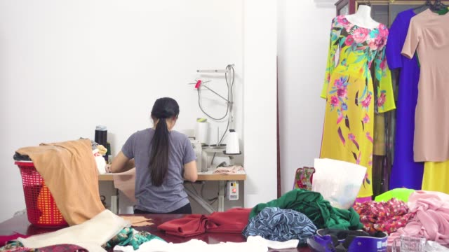 woman making ao dai vietnamese traditional clothing using sewing machine in a clothing design studio - fashion designer stock videos and b-roll footage