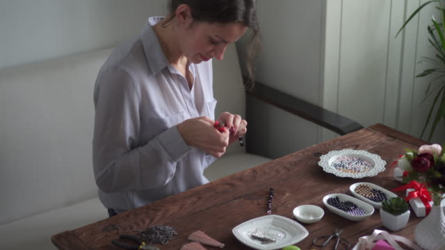 woman making beaded earrings using pliers - bracelet stock videos and b-roll footage