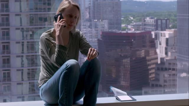stockvideo's en b-roll-footage met woman making business call from hotel room overlooking downtown austin - zakenreis