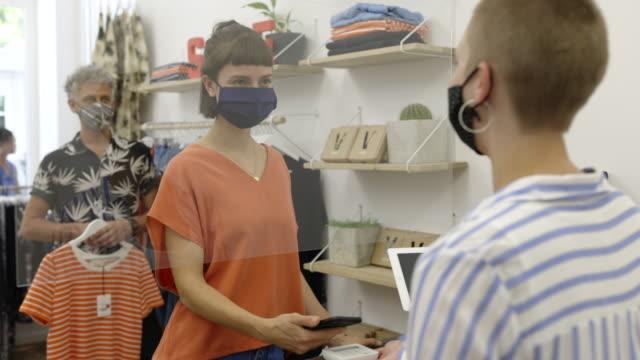 donna che effettua pagamenti contactless nel negozio di moda - negozio di abbigliamento video stock e b–roll