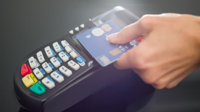 Woman making contactless payment with credit card