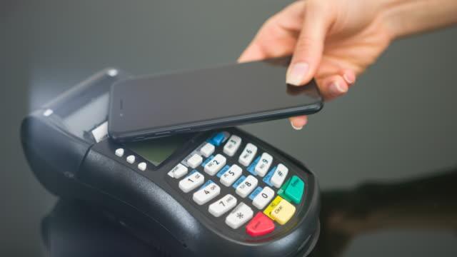 vídeos de stock, filmes e b-roll de mulher fazendo pagamento sem contacto com smartphone - compra com cartão de crédito