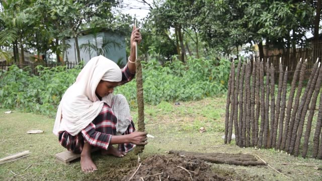 a woman making cow dung fire stick to prepare food in a remote village in goalpara assam india on 19 december 2019 dried cow dung bar or sticks made... - cooking stock videos & royalty-free footage