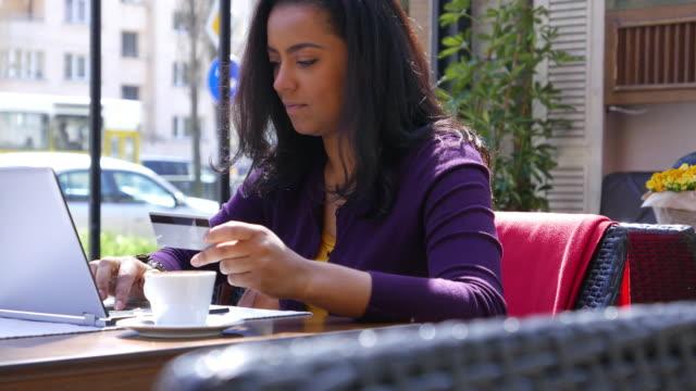 frau macht kreditkarte kaufen - internet café stock-videos und b-roll-filmmaterial