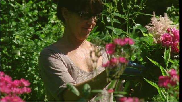 cu, woman making flower bouquet in garden, brussels, belgium - gardening glove stock videos & royalty-free footage