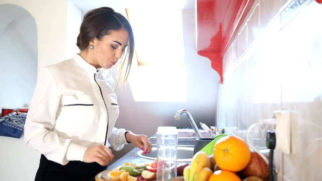 Woman making healthy fruit smoothies in her kitchen