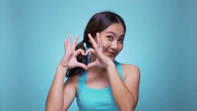 woman making heart shape on isolated blue background 4k - falling in love stock videos and b-roll footage