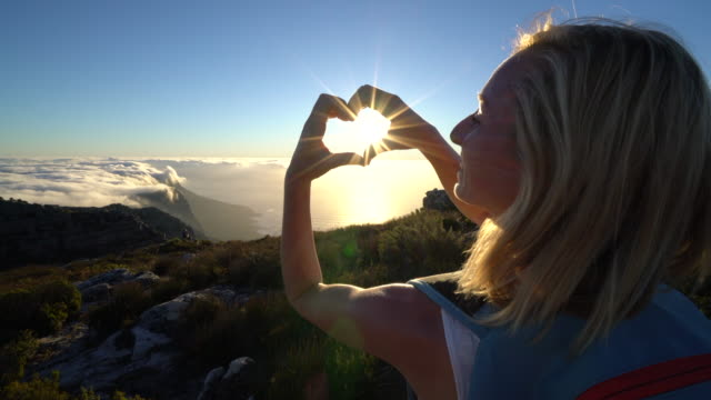 Woman making heart shape with hands on Table Mountain