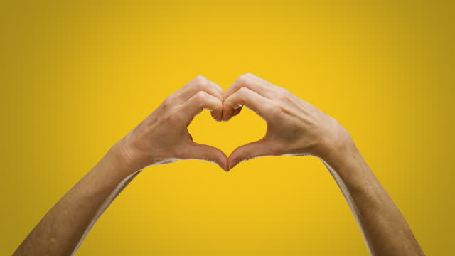 cu woman making heart shape with hands - yellow stock videos & royalty-free footage